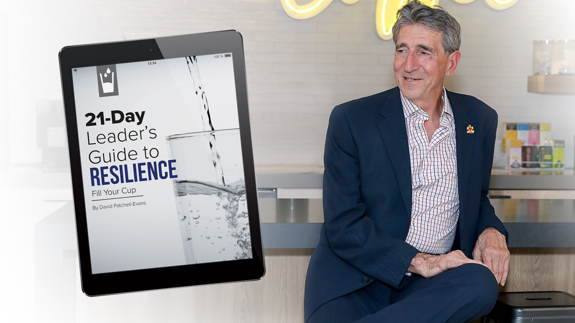 David Patchell Evans sitting gracefully next to a tablet that says 21-Day Leader's Guide to Resilience